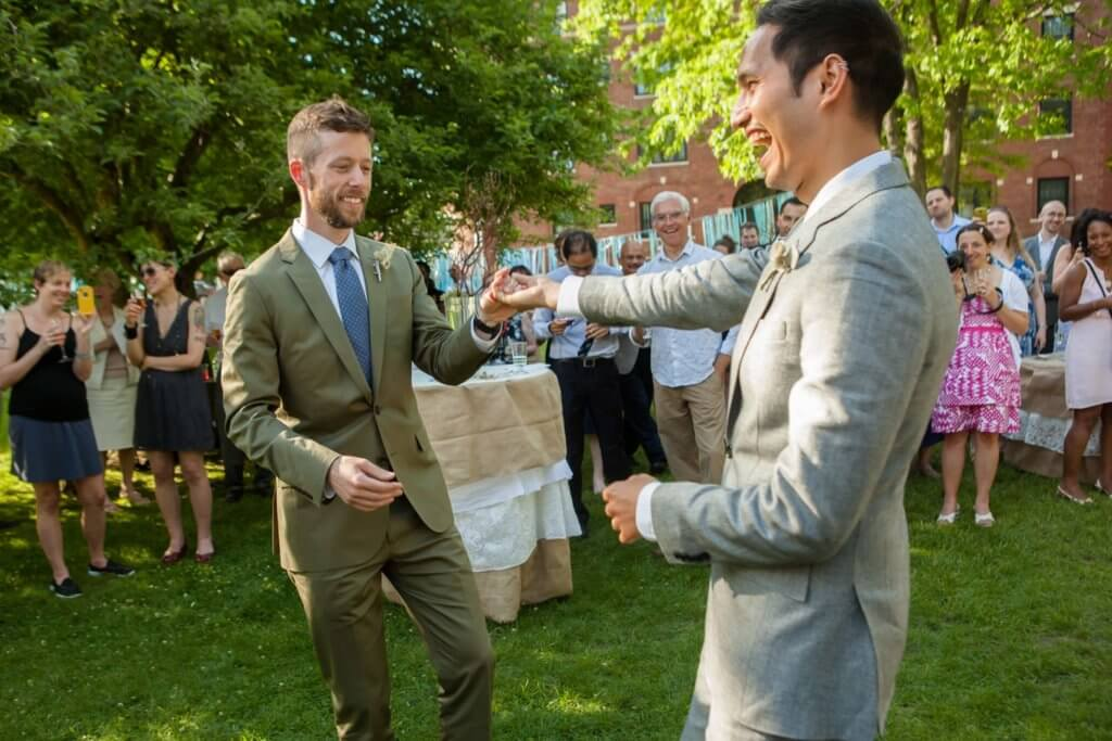 Newlyweds (two grooms) dancing in garden setting