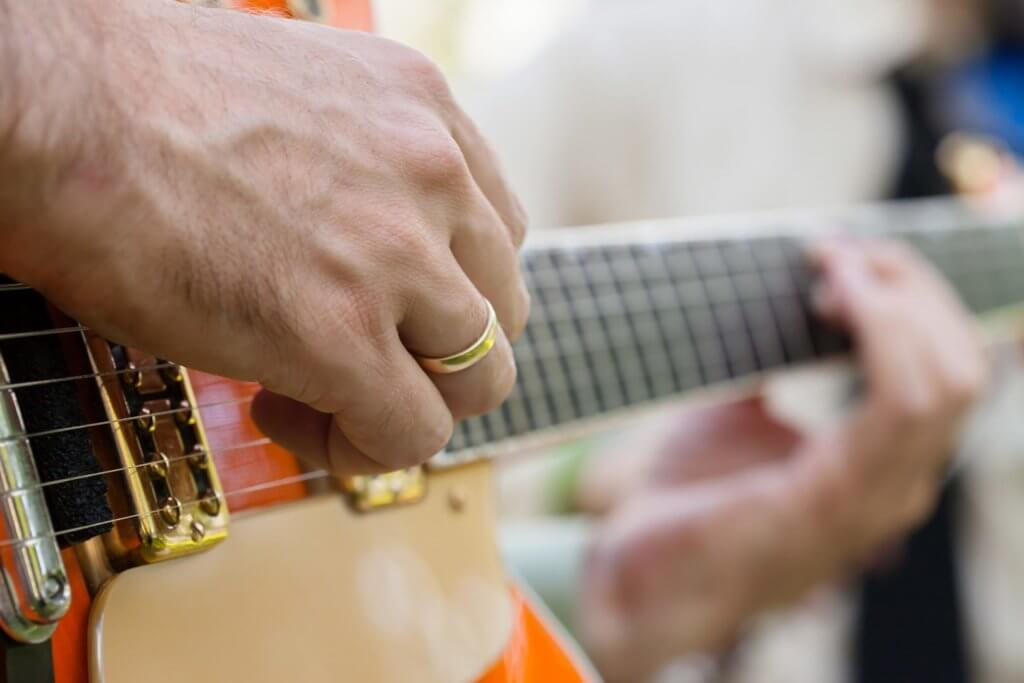 Man playing guitar, focus on hand with wedding band