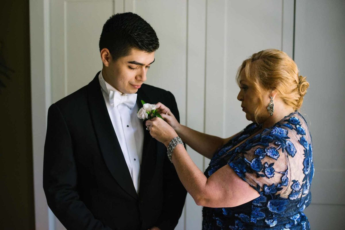 Mother of the groom pinning the boutonniere on her son, the groom.
