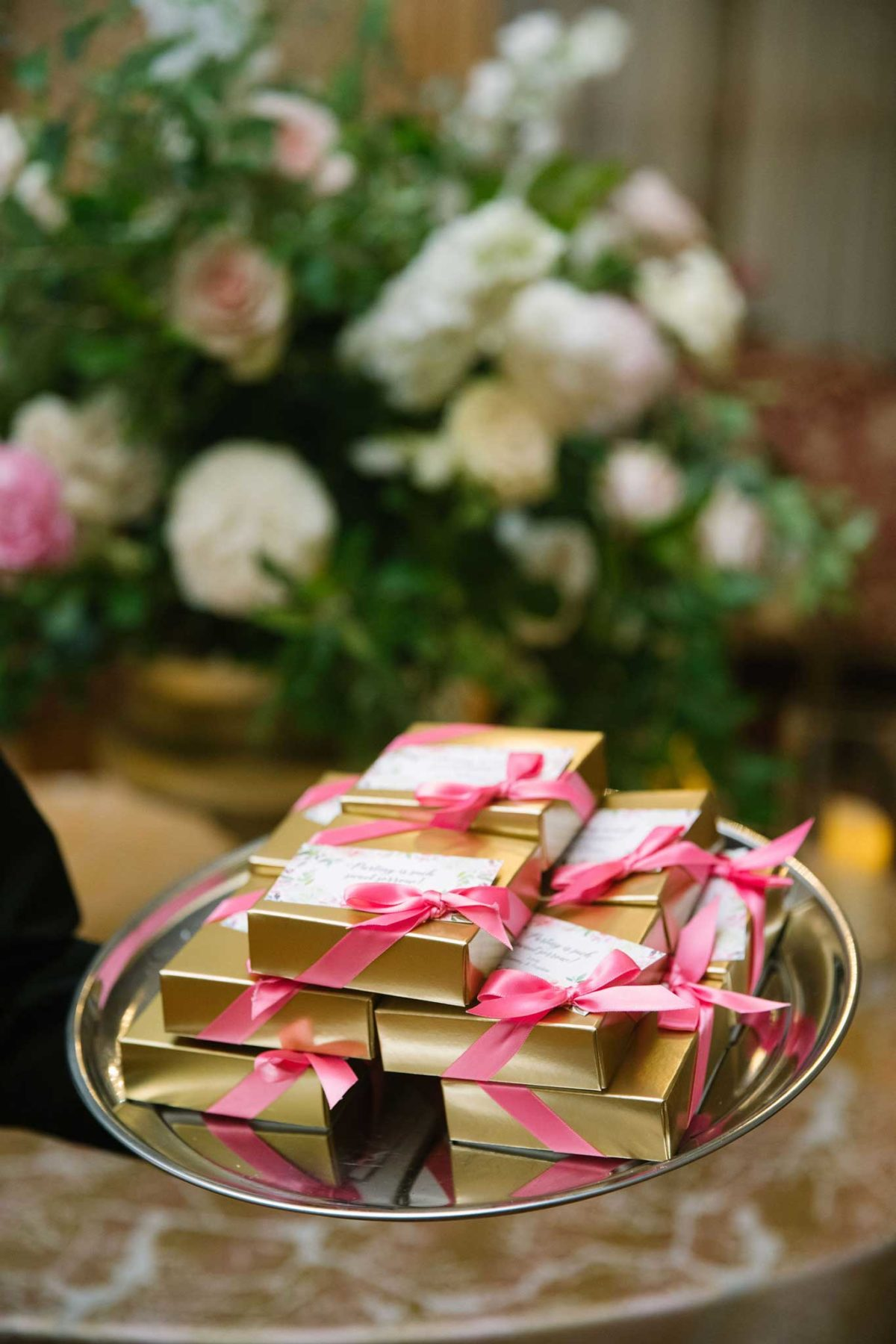 Wedding Favors: gold foil chocolate boxes tied with a pink ribbon, adorned with a handpainted favor tag.