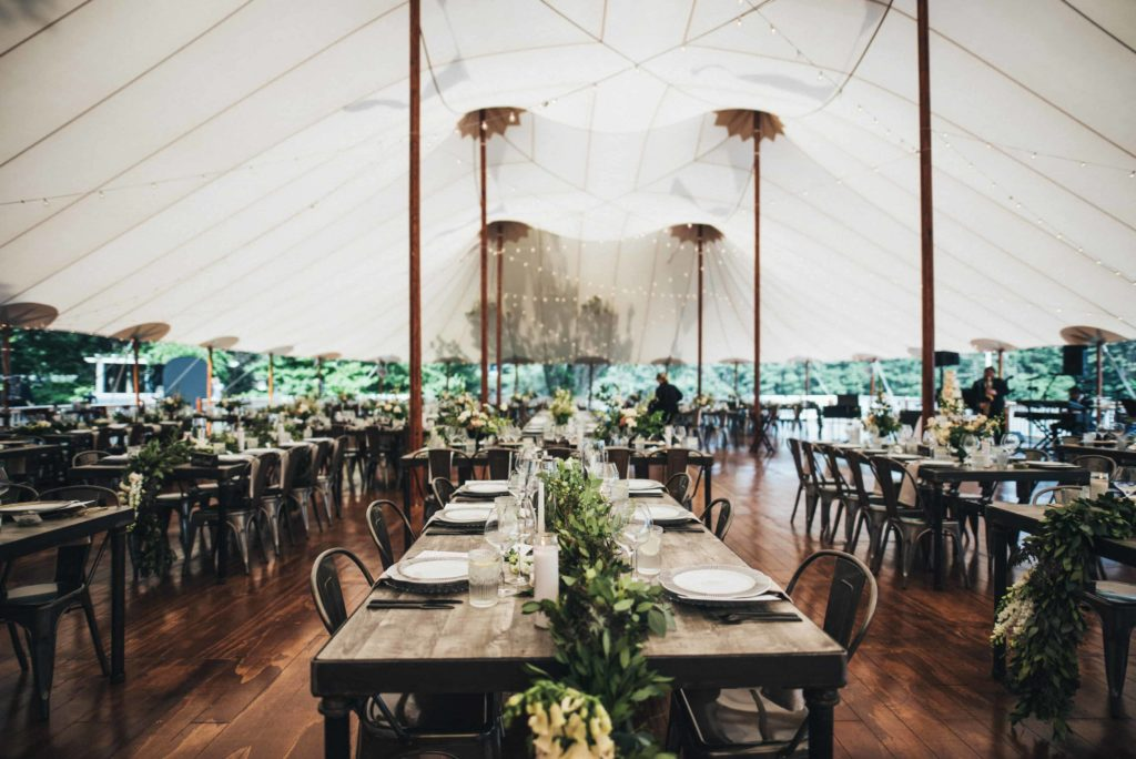 Wedding reception tent with wooden family style tables